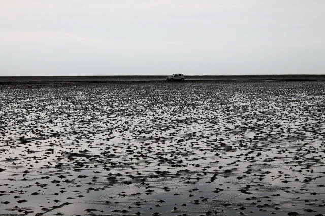 A car crosses the causeway at low tide