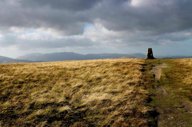 A lone walker takes a break on the top of Loadpot Hill